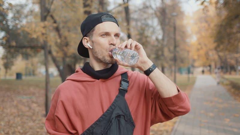 Mann trinkt Wasser, nachdem Haartransplantation ambulant durchgeführt wurde.