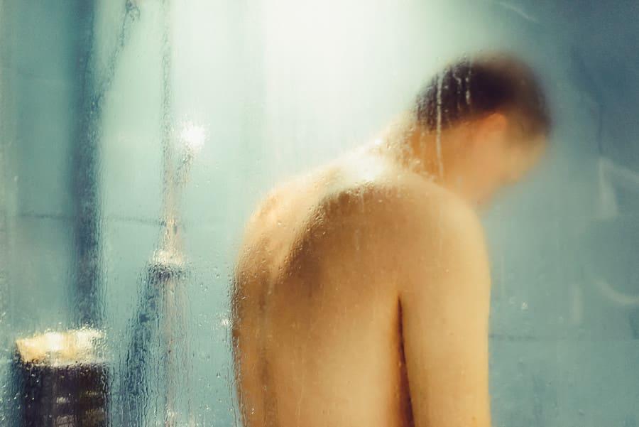 Mann unter der Dusche nach Haartransplantation.
