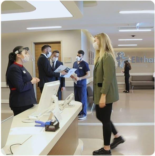 Junge Frau unterhält sich an der Klinikrezeption mit einer Mitarbeiterin