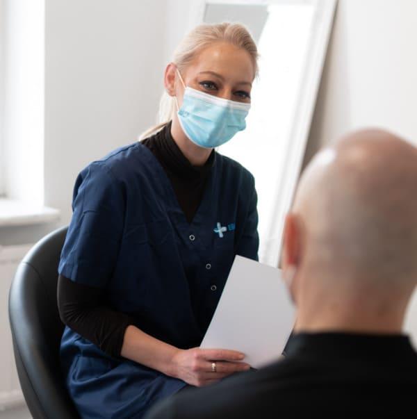Ein Mitglied des Elithair Teams aus Düsseldorf mit einem Patienten