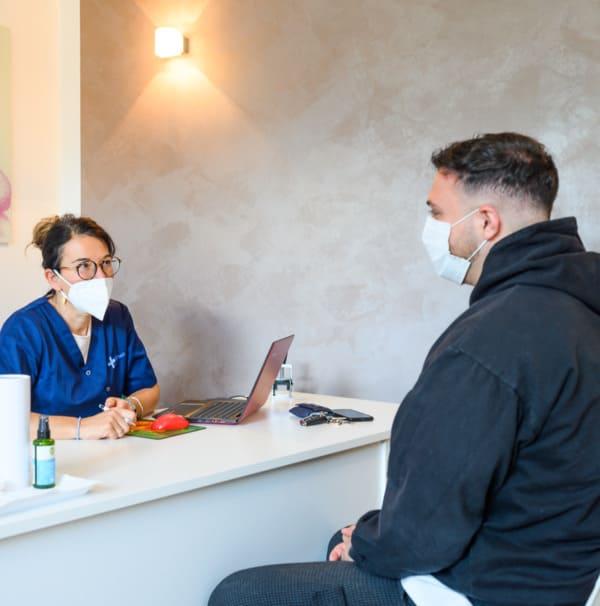 Beratung eines Teammitglieds mit einem Patienten bei Elithair in München