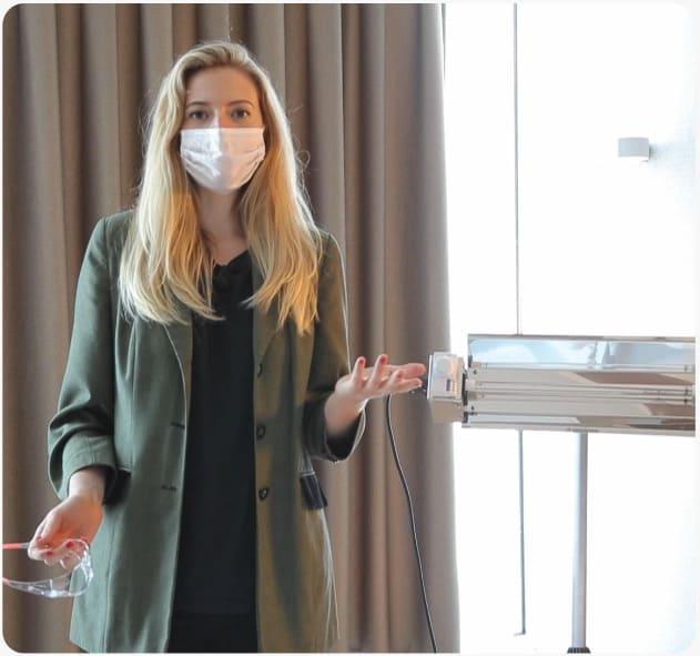 Junge Frau im Behandlungsraum weist auf die vorhandene UV-Lampe gegen Bakterien hin