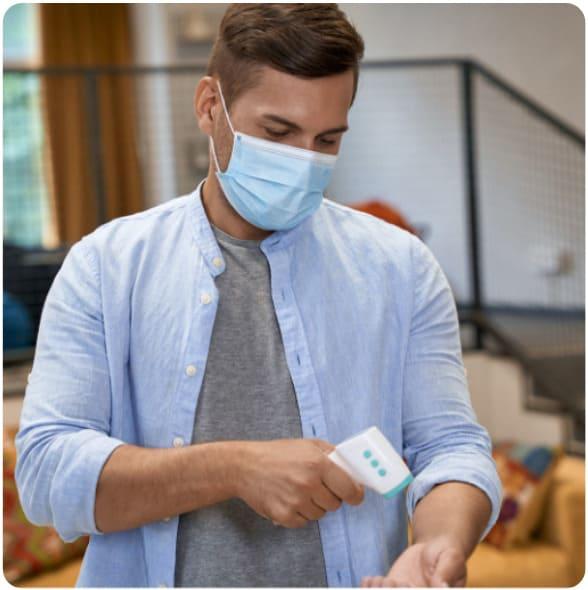 Junger Mann prüft seine Körpertemperatur mit einem kontaktlosen Fiebermessgerät
