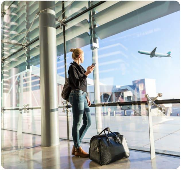 Frau mit Gepäck am Flughafen schaut zu wie ein Flugzeug gerade startet