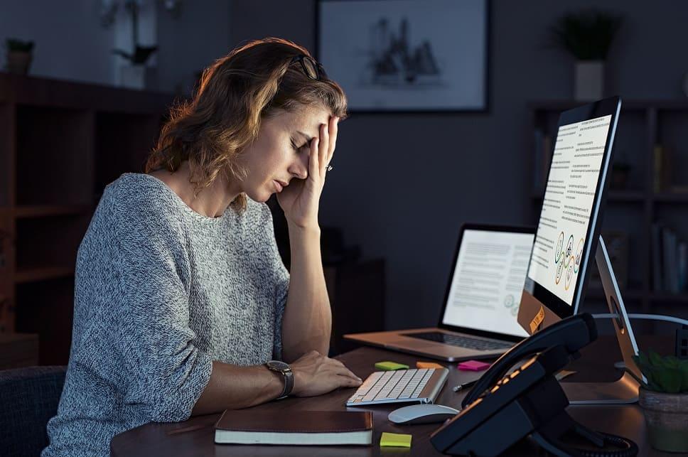 Eine gestresste Frau hält sich die Hand ins Gesicht und schaut nach unten