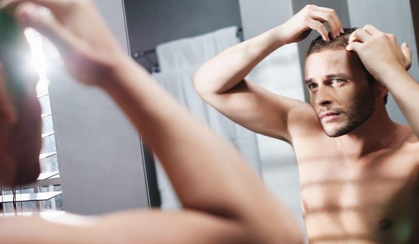 Einseitiger Haarausfall Junge Mann vor dem Spiegel