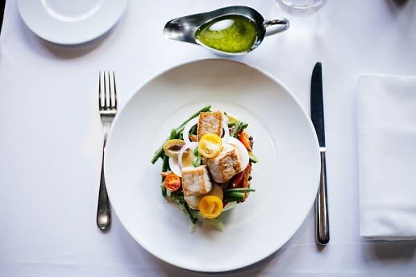Teller mit gesundem Gericht von oben, Messer und Gabel an den Seiten, auf weißem Tischtuch
