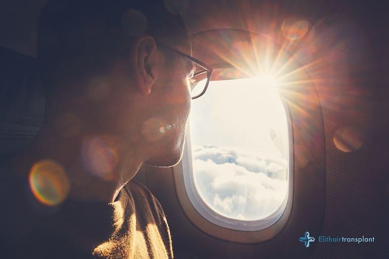 Fliegen nach Haartransplantation - Mann sitzt im Flugzeug und schaut duch das Fenster