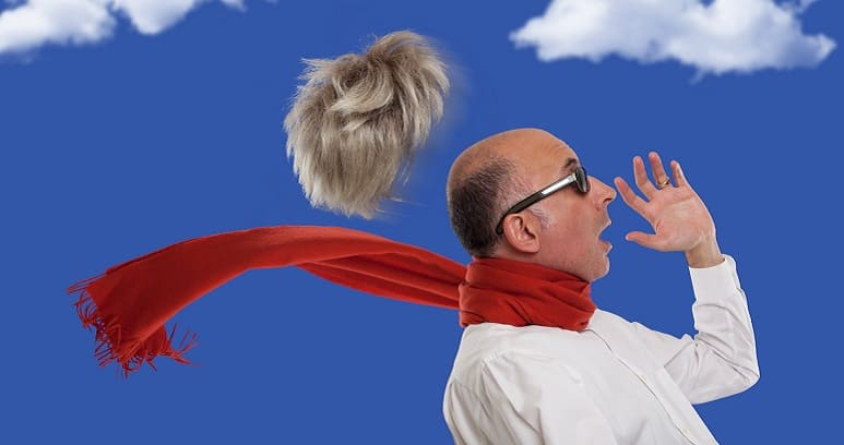 Mann mit Schaal guck erschrocken, da sein Toupe durch den Wind abgeflogen ist