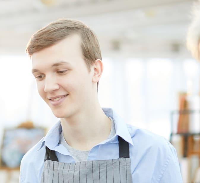 Sehr junger Mann mit Geheimratsecken in Arbeitskleidung