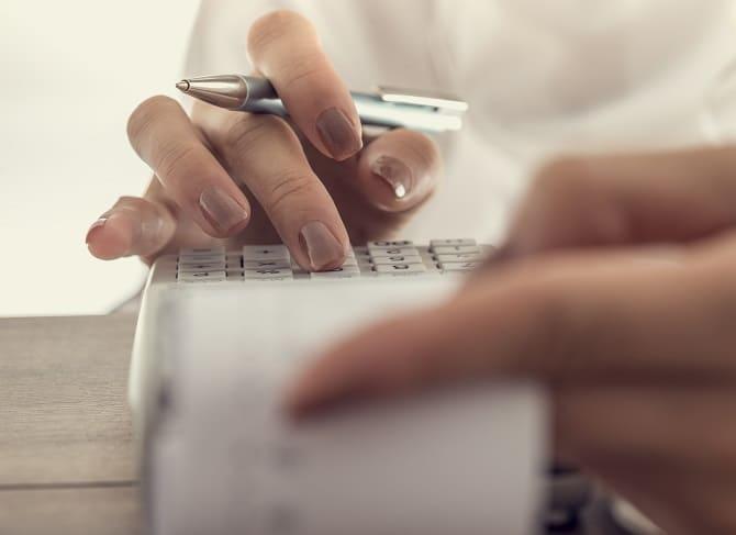 Frauenhand am Kalkulieren von Kosten an einer Rechenmaschine
