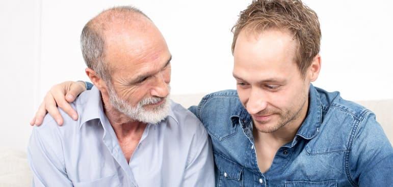 Genetischer Haarausfall - Ein junge und ein alte halbglatzer Mann sitzen zusammen