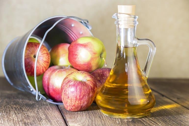 Äpfel in einem Eimer neben einer Flasche Apfelessig auf einem Holztisch