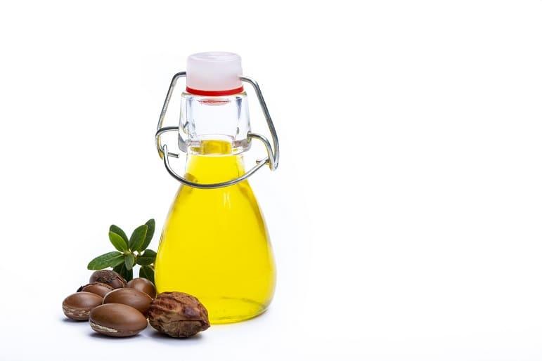 Argannüsse liegen neben einer Flasche mit Arganöl