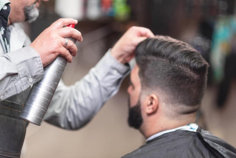 Mann beim Friseur wird mit Haarspray gestyled