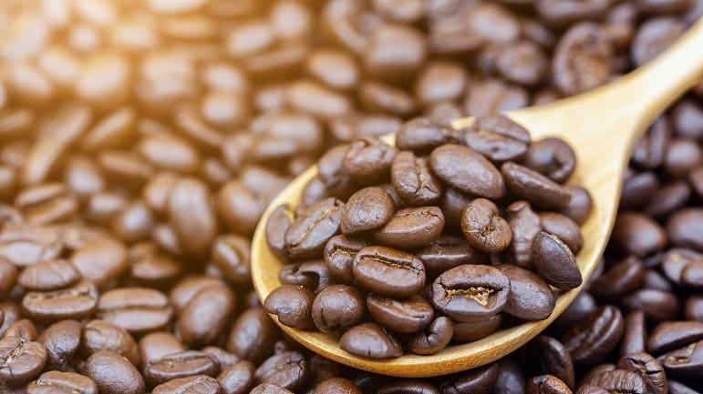 Kaffeebohnen auf einem Holzlöffel liegend auf ganz vielen weiteren Kaffebohnen