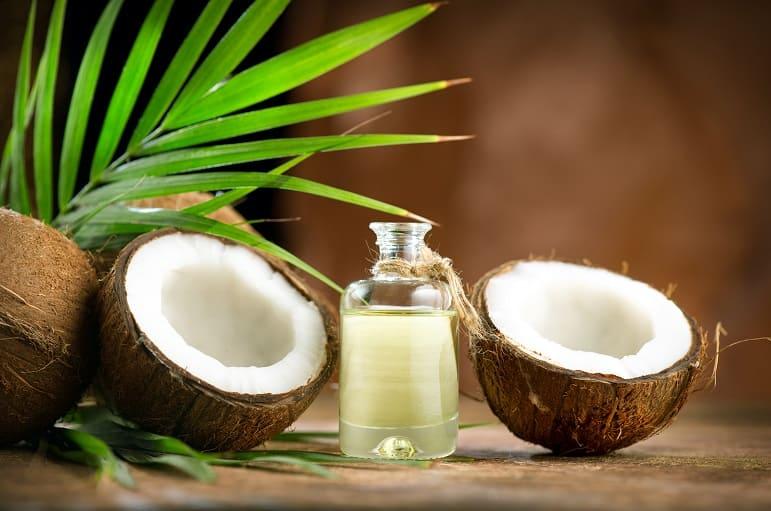 Kokonüsse und Öl neben einem grünen Palmenblatt