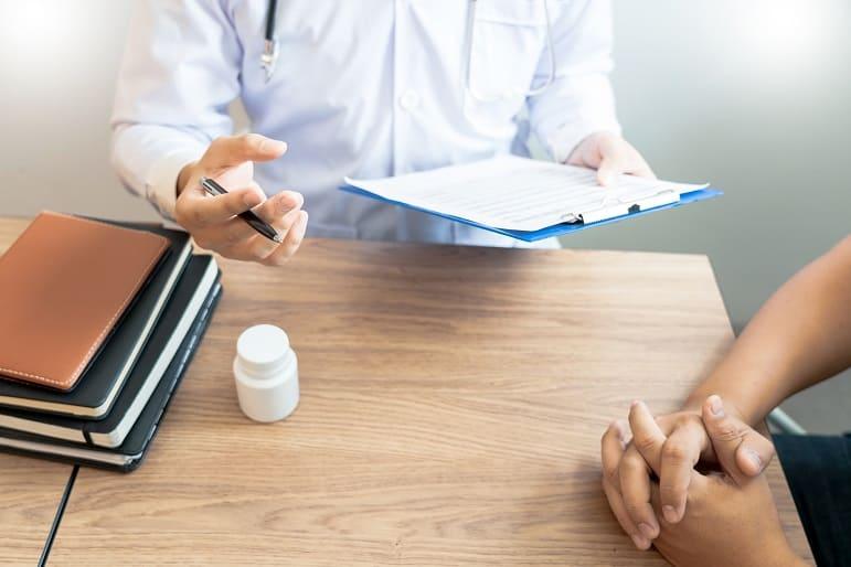 Arzt erklärt Patienten seine Diagnose bezüglich des Haarausfalls