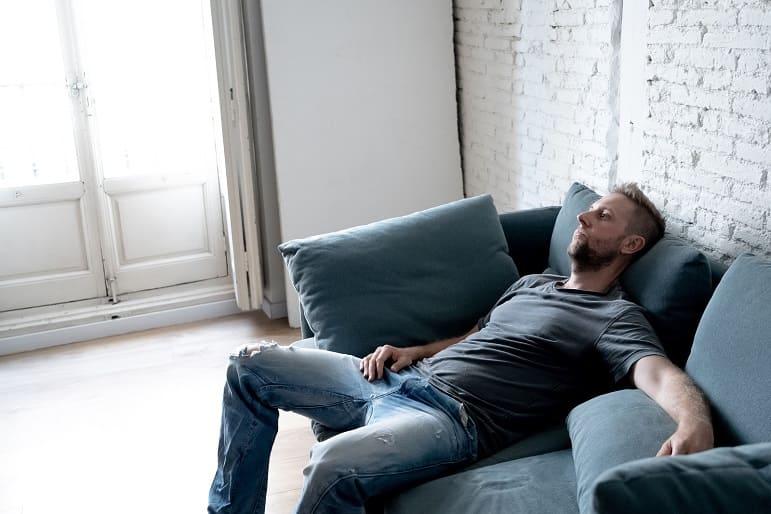 Mann sitzt nachdenklich und depressiv auf der Couch