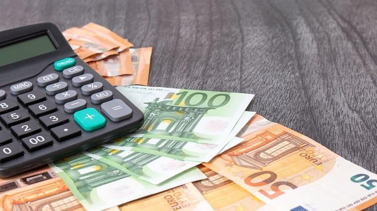 Taschenrechner neben 100 Euro und 50 Euro Banknoten