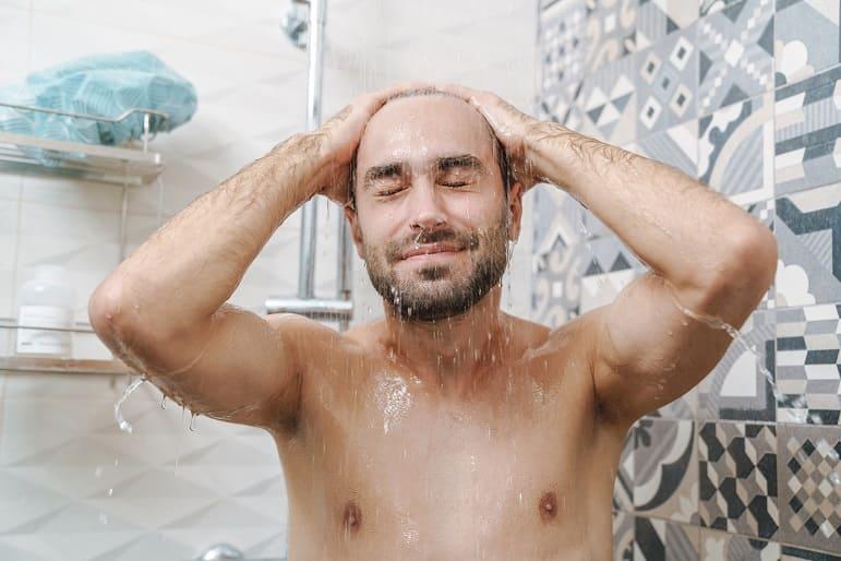 Lächender Mann beim Haare waschen unter der Dusche