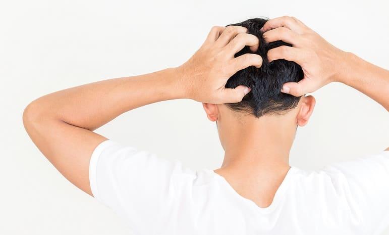 Mann kratzt sich von hinten am Kopf