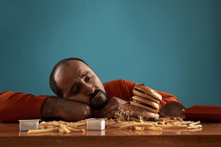 Mann mit Bart und Halbglatze sitzt vor Hamburger und Pommes
