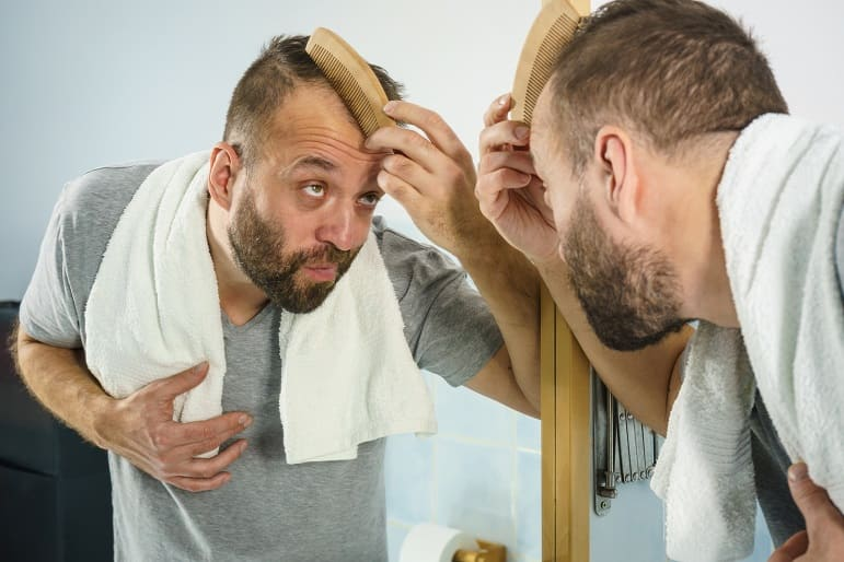 Mann steht vor dem Spiegel und kämmt seine dünnen Haare
