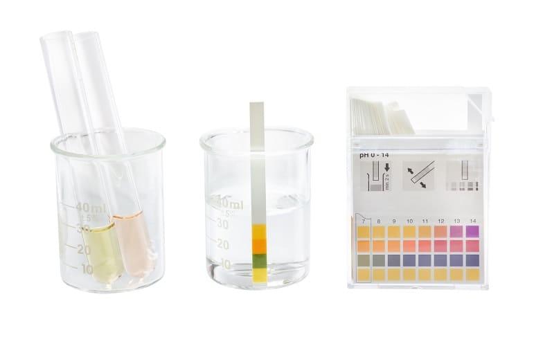 Meßbecher mit pH Testern als Inhalt