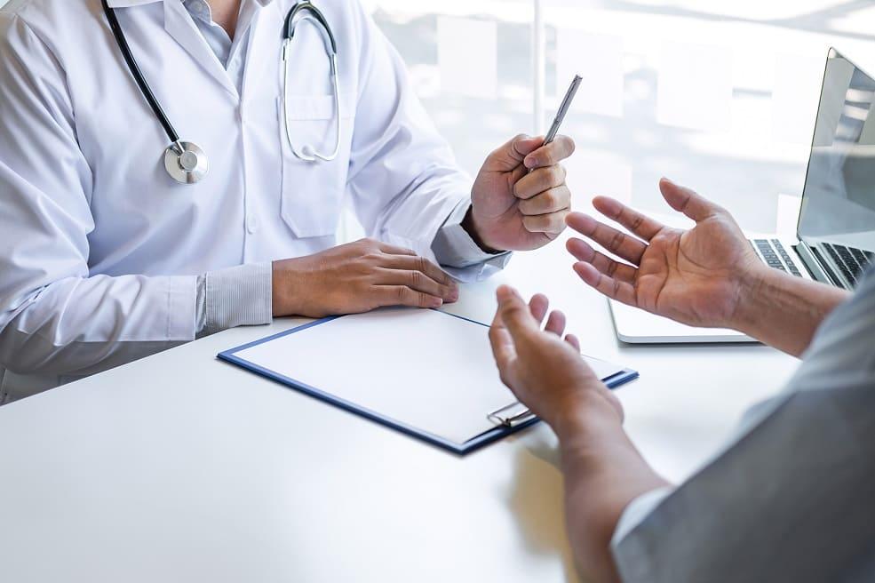 Arzt und Patient sitzen sich gegenüber und besprechen die Diagnose nach dem Bluttest bei Haarausfall