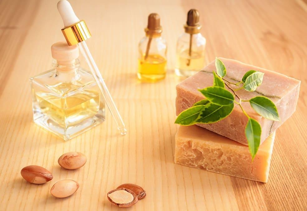 Behälter mit Arganöl neben weiteren Flaschen und handgemachter Seife auf einem Holztisch