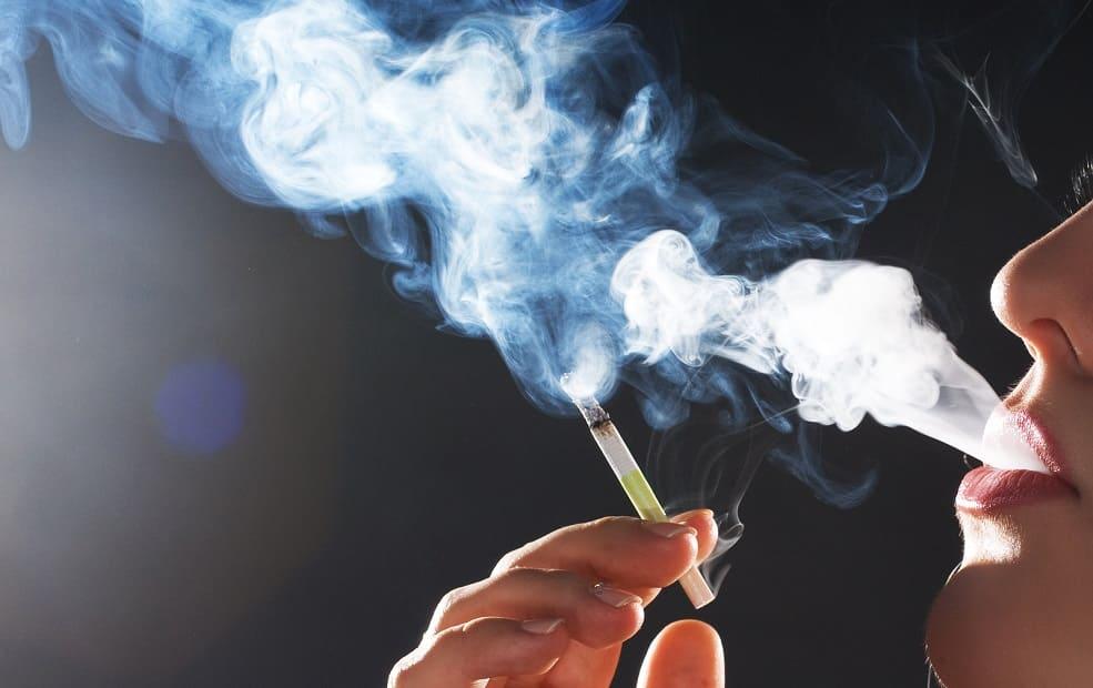 Frau pustet Zigarettenrauch in die Luft