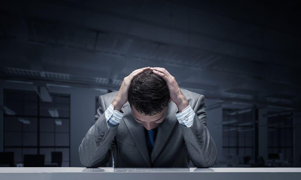 Gestresster Geschäftsmann im grauen Anzug schlägt beide Hände über den Kopf