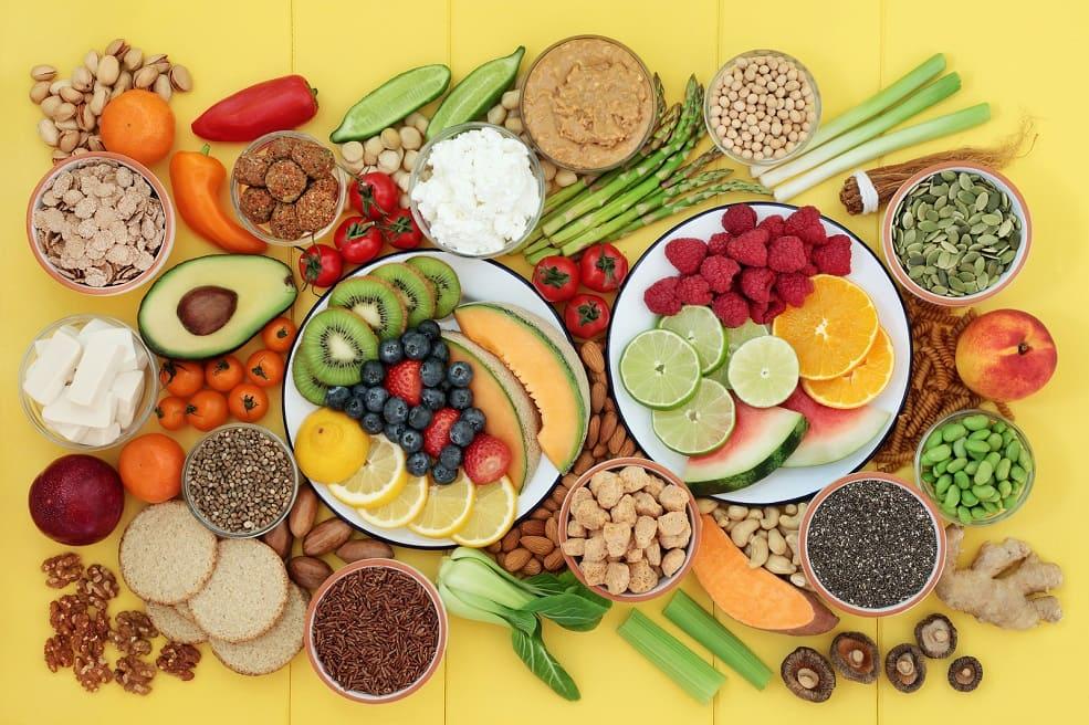 Verschiedenes gesundes Obst und Gemüse auf einem gelben Holztisch