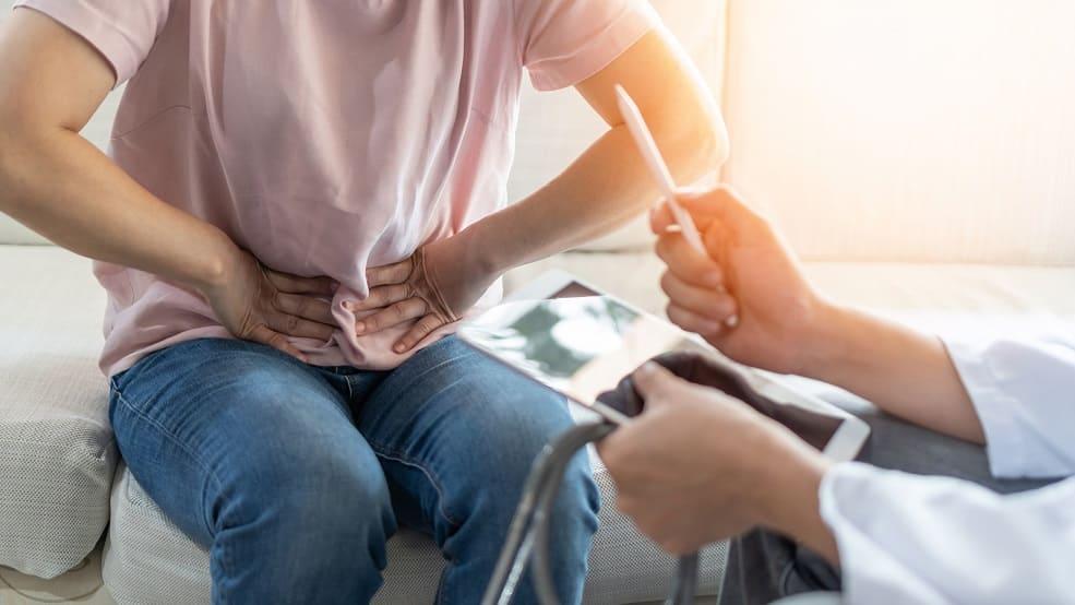 Patient sitzt dem Arzt gegenüber und hält sich vor Schmerzen mit beiden Händen die Magengegend