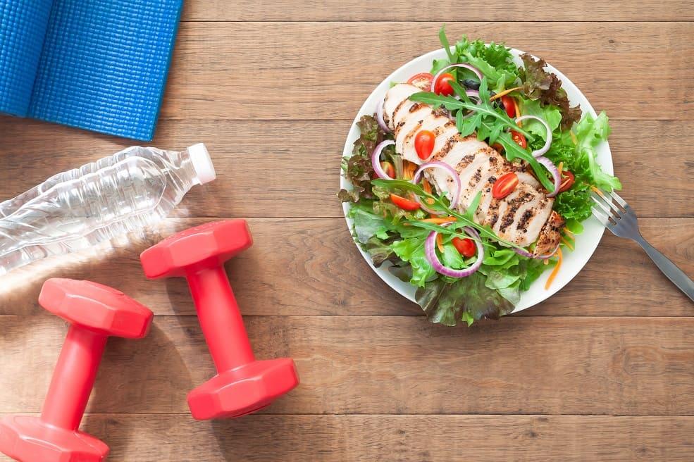 Blaue Trainingsmatte, Flasche Wasser, Hanteln und ein Teller mit gesundem Essen und Gabel auf einem Holztisch