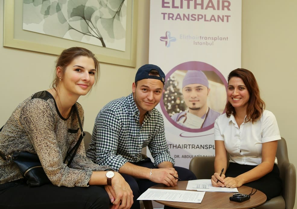 Zwei weibliche Elithairtransplant Mitarbeiter bei der Beratung mit einem männlichen Patienten