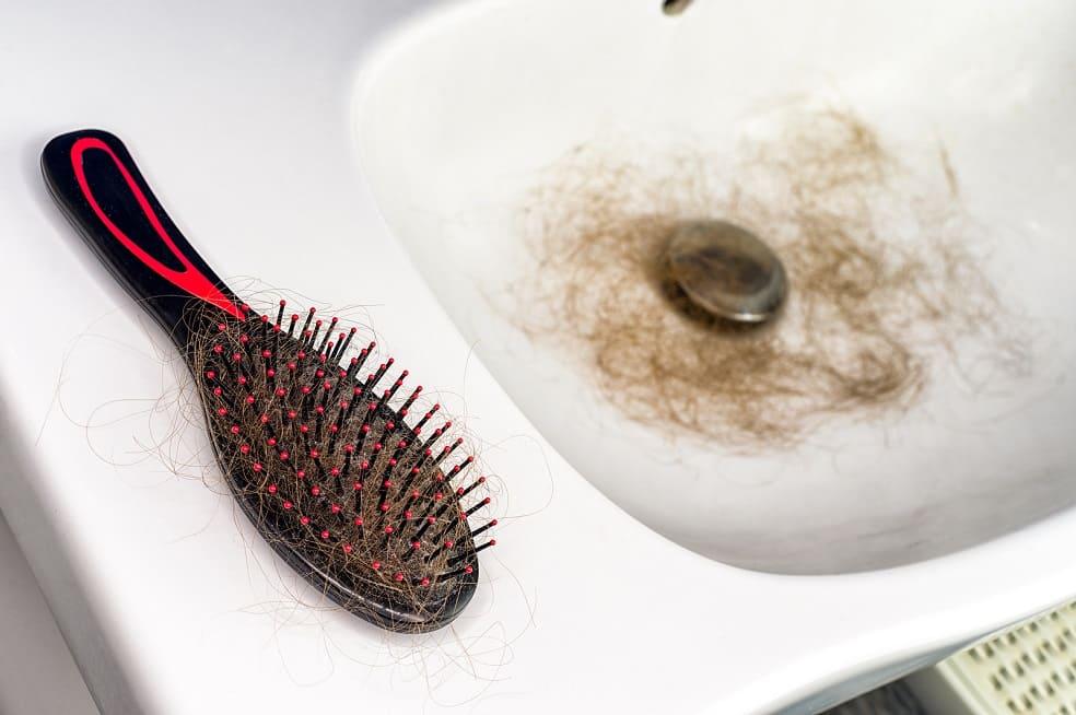 Haarbürste liegt auf einem Waschbecken in welchem ein Büschel ausgefallener Haare liegt