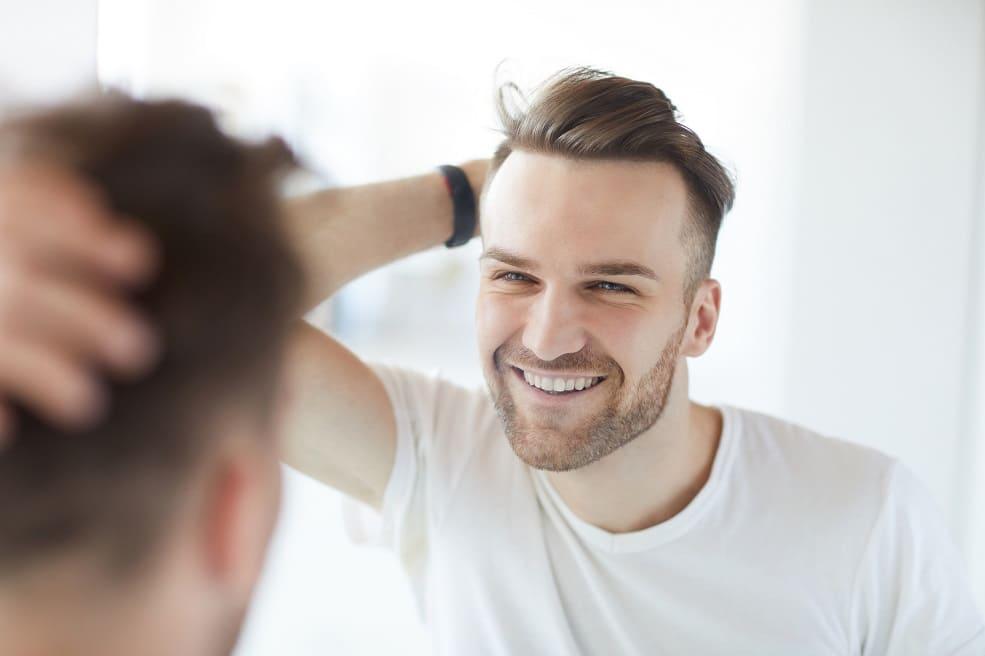 Junger Mann mit vollem Haar begutachtet das Ergebnis seiner Haartransplantation im Spiegel