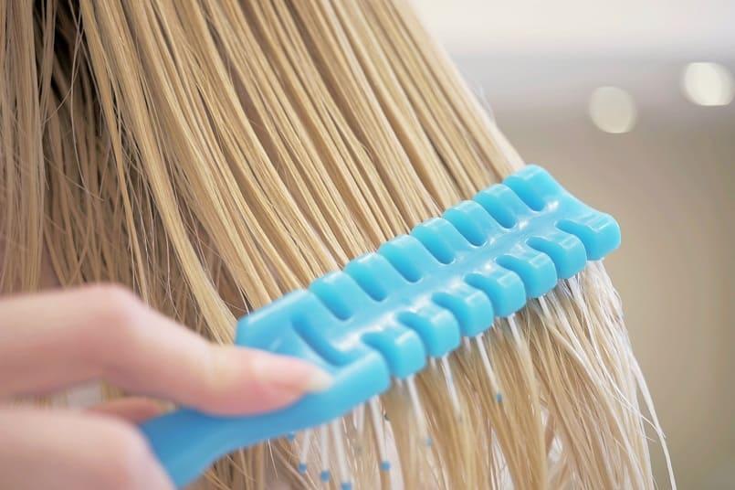 Frau kämmt sich ihre blonden Haare in der Nahaufnahme