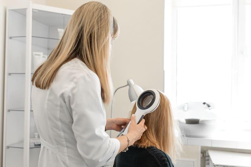 Dermatologin prüft den Status der Haare bei einer Patientin