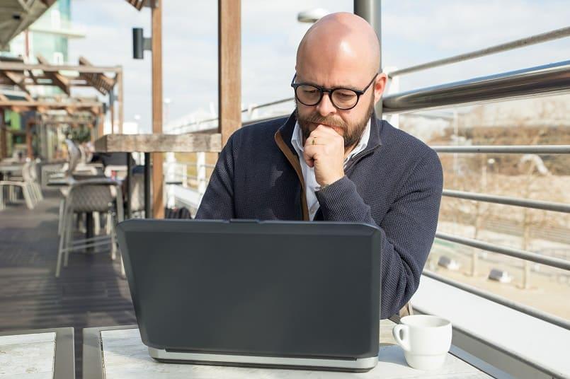 Mann mit Glatze sitzt nachdenklich in einem Cafe mit offenem Laptop