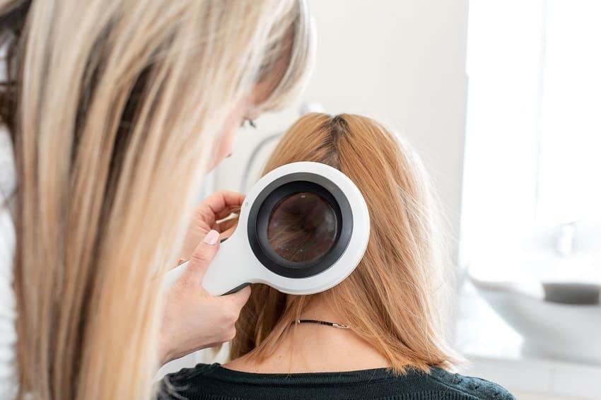 Dermatologin prüft unter einer großen Lupe den Hinterkopf einer Frau