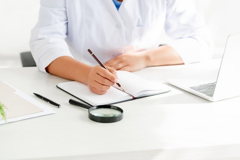 Dermatologin hat Schreibunterlagen und eine Lupe neben ihrem Laptop auf dem Tisch