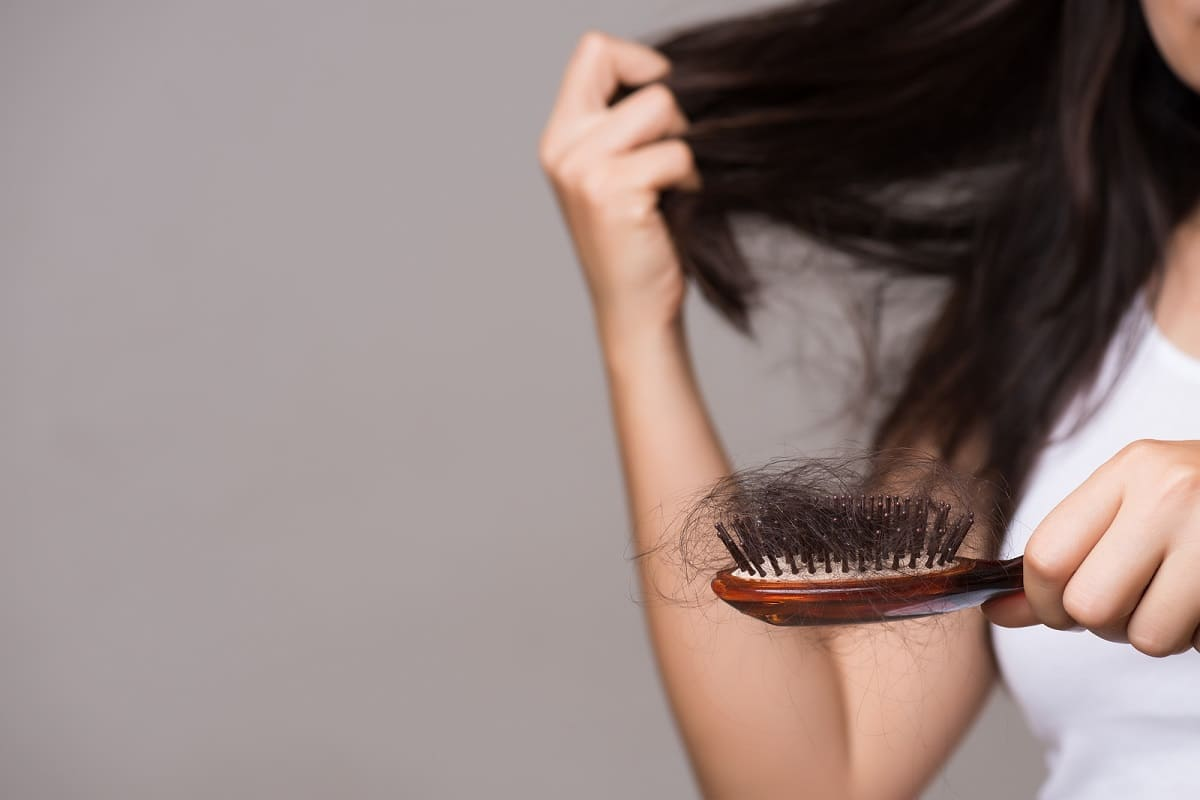 Eine Frau sieht viele ausgefallene Haare in ihrer Brüste
