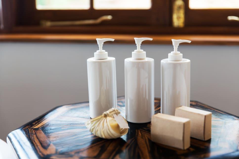 Drei Flaschen mit Haarwaschmittel stehend auf einem kleinen runden Holztisch