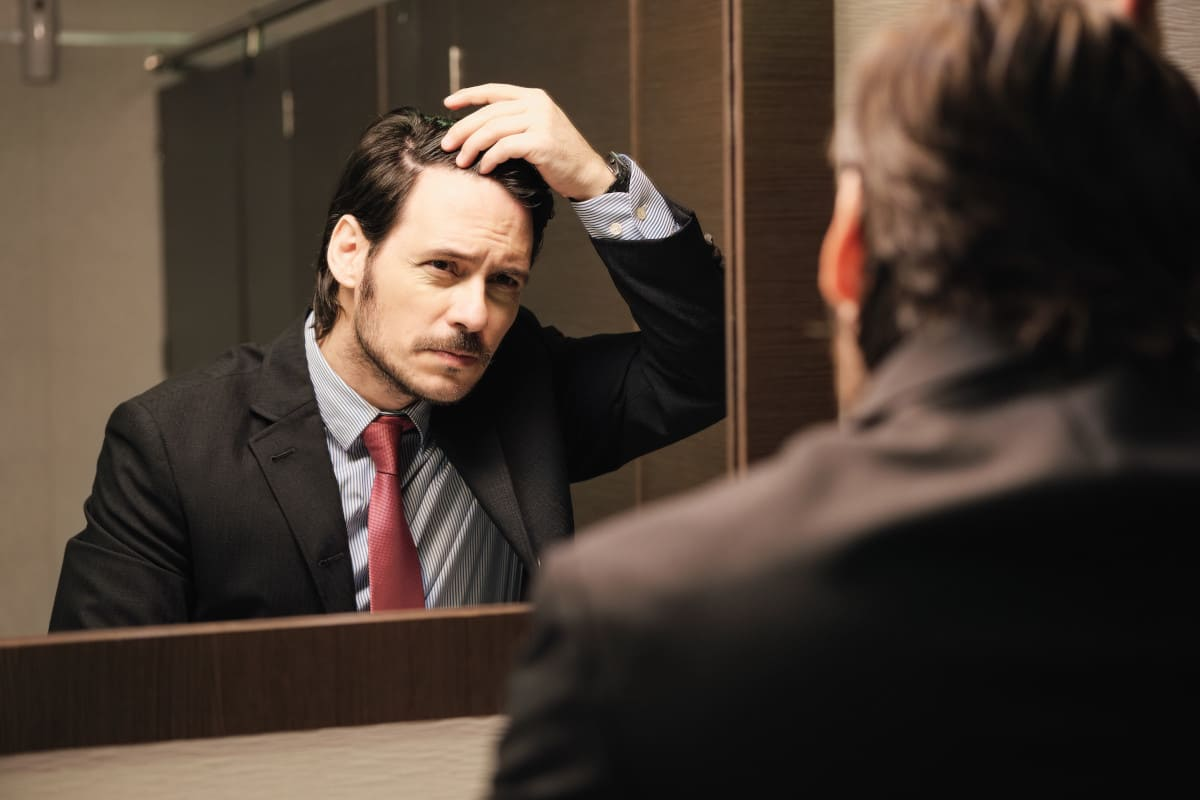 Haarausfall vorbeugen - Mann vor dem Spiegel
