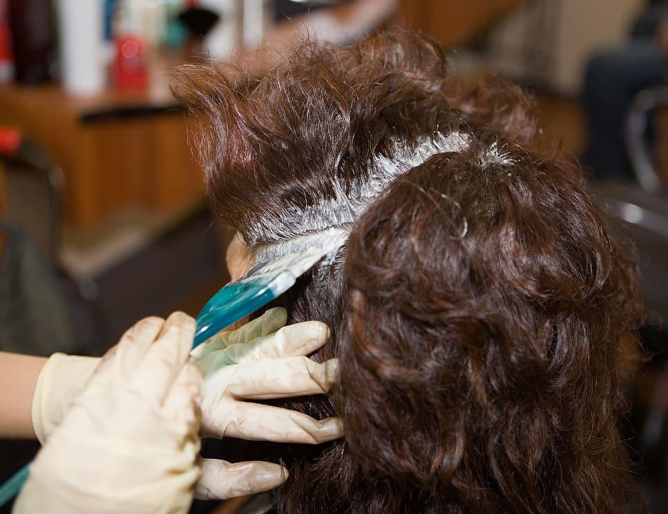 Frau lässt sich die Haare beim Friseur tönen