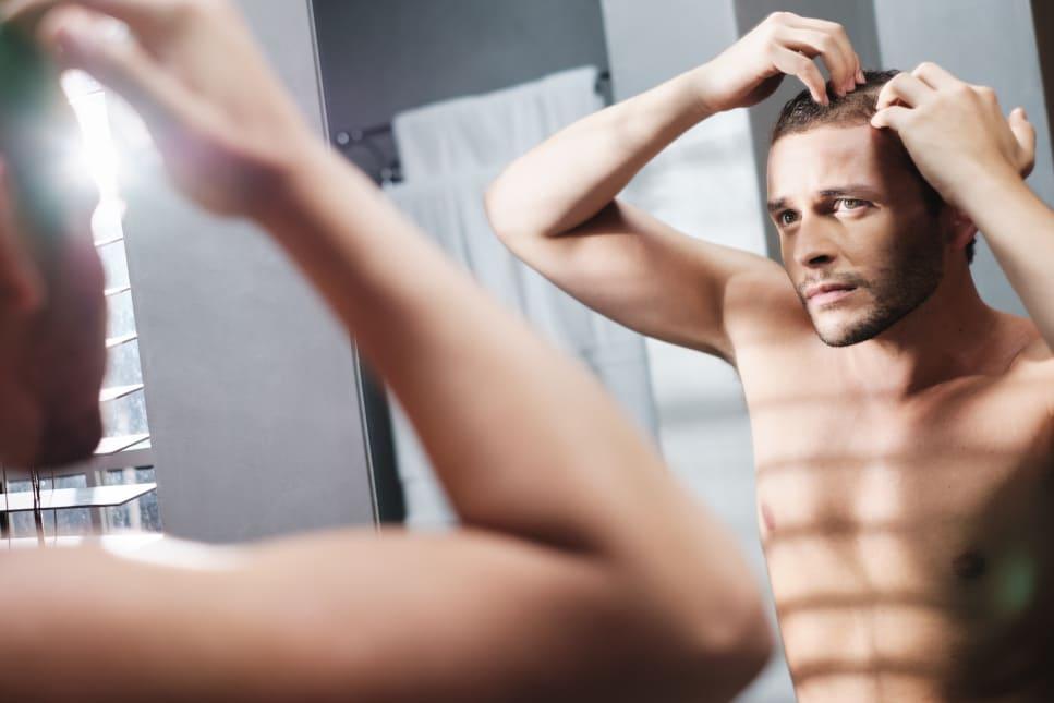 Mann begutachtet seinen Haarausfall im Badezimmerspiegel