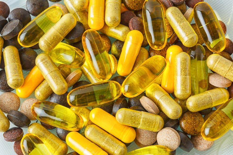 Verschiedene Vitamin Tabletten und Nahrungsergänzungsmittel liegend übereinander